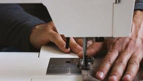 Paño masculino de la tenencia de la mano de la costurera de la vista delantera detrás de la máquina de coser almacen de video