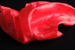 Pañuelo de seda rojo vivo brillante en el terciopelo negro Foto de archivo libre de regalías