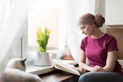 Pañuelo que lleva del enfermo de cáncer joven de la hembra adulta que se sienta en la cocina con su gato del animal doméstico imagen de archivo libre de regalías
