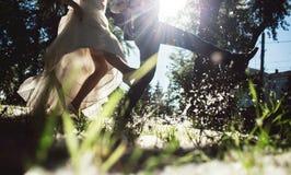 Państwa młodzi kopnięcia topolowy fluff w parku Zbliżenie nogi Ślubny rozrywki pojęcie Obraz Royalty Free