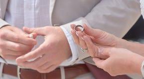 Państwa Młodzi mienia ręki i wymieniać pierścionki fotografia stock