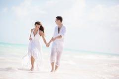Państwo młodzi bieg na tropikalnej plaży obraz stock