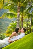 Państwo młodzi buziak delikatnie na zielonej trawie przeciw drzewkom palmowym w lecie obraz stock