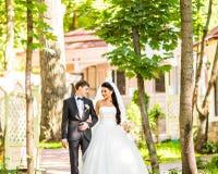 Państwo Młodzi chodzi Outdoors na wiosny naturze przy dniem ślubu Bridal para, Szczęśliwa nowożeńcy kobieta i mężczyzna obejmowan Zdjęcia Stock