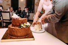 Państwo młodzi ciie poziom czekoladowy ślubny tort z białymi kwiatami dekoruje Zdjęcia Royalty Free