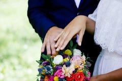 Państwo młodzi demonstruje pierścionki na ich rękach przeciw kwiatu bukietowi jako tło Zdjęcia Stock