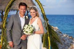 Państwo Młodzi Dostaje Poślubiający W Plażowej ceremonii Fotografia Stock
