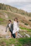 Państwo młodzi iść dla spaceru w Carpathians górach Obraz Stock
