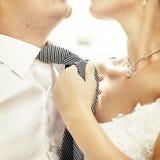 Państwo młodzi. Kobiety ciągnięcie dalej obsługuje krawat. Zdjęcia Stock