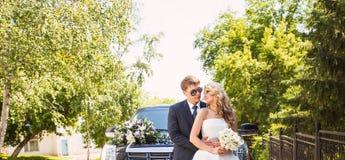 Państwo młodzi nad ślubnym samochodowym tłem zdjęcie stock