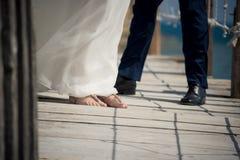 Państwo młodzi pokazuje daleko ich buty na molu przy to out zdjęcie stock