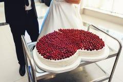 Państwo młodzi prepairing dla ciąć dużego ślubnego tort w formie serca Na odgórny swój zakrywającym z truskawkami fotografia stock