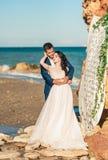 Państwo młodzi przy ślubną ceremonią blisko morza Obrazy Royalty Free