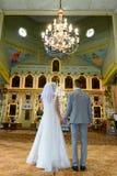 Państwo młodzi przy kościół podczas ślubnej ceremonii obraz stock