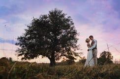 Państwo młodzi stoi obok wielkiego drzewa, po ślubnej ceremonii Sylwetki fotografia w ciepłych kolorach Zdjęcie Stock