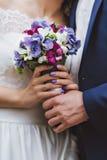 Państwo młodzi trzyma bridal bukieta zakończenie up Fotografia Stock