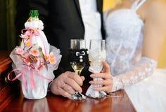 Państwo młodzi trzyma pięknie dekorujących ślubnych szkieł wi Fotografia Stock