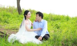Państwo młodzi w ślubnej sukni z elegancką fryzurą z białym ślubnej sukni obsiadaniem w trawie rzeką, Obraz Stock