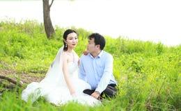 Państwo młodzi w ślubnej sukni z elegancką fryzurą z białym ślubnej sukni obsiadaniem w trawie rzeką, Zdjęcia Royalty Free