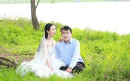 Państwo młodzi w ślubnej sukni z elegancką fryzurą z białym ślubnej sukni obsiadaniem w trawie rzeką, Obraz Royalty Free