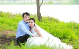 Państwo młodzi w ślubnej sukni z elegancką fryzurą z białym ślubnej sukni obsiadaniem w trawie rzeką, Zdjęcia Stock