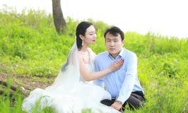 Państwo młodzi w ślubnej sukni z elegancką fryzurą z białym ślubnej sukni obsiadaniem w trawie rzeką, Zdjęcie Stock