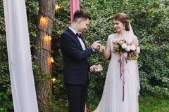 Państwo młodzi wymiana dzwoni podczas ślubnej ceremonii, ślub w lato zieleni ogródzie z retro żarówkami obraz royalty free