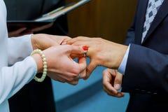Państwo młodzi z obrączkami ślubnymi poślubia przy ceremonią Panna młoda ubiera w śmietanki koronki ślubnej sukni Fornal jest ubr Zdjęcie Stock