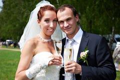 Państwo młodzi z szampańskimi szkłami Zdjęcia Stock