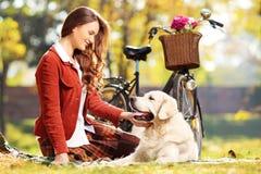 在草的美好的女性开会和看她的在pa的狗 免版税库存图片