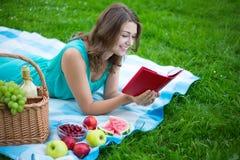 有野餐篮子的美丽的妇女和果子在pa的阅读书 图库摄影