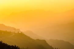PA Sa, город в горах на заходе солнца стоковые изображения