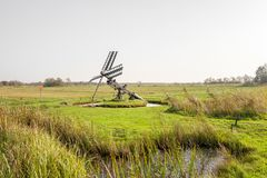 Paaltjasker windmill in Kalenberg in Friesland, Netherlands. Paaltjasker windmill in Kalenberg meadow  in Friesland, in the Netherlands Royalty Free Stock Photos