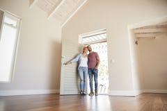 Paar-Öffnungs-Tür und Gehen in leeren Aufenthaltsraum des neuen Hauses lizenzfreies stockbild