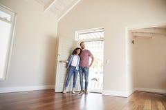 Paar-Öffnungs-Tür und Gehen in leeren Aufenthaltsraum des neuen Hauses lizenzfreie stockbilder