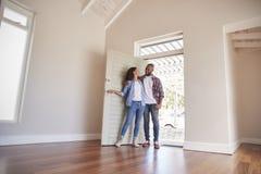 Paar-Öffnungs-Tür und Gehen in leeren Aufenthaltsraum des neuen Hauses lizenzfreie stockfotos