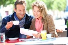 Paar aan tablet het drinken koffie wordt verbonden die Royalty-vrije Stock Afbeelding