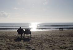 Paar als voorzitter op strand met hond het lopen Stock Afbeeldingen