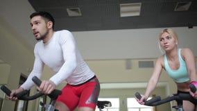 Paar atleten die op hometrainers versnellen stock videobeelden