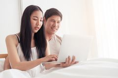 Paar auf Bett benutzt Laptop zusammen stockbild