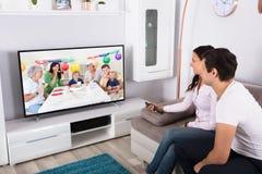 Paar-aufpassende Geburtstags-Feier im Fernsehen stockfotos