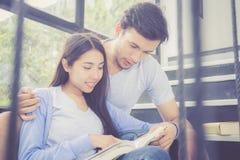 Paar Aziatische knappe man en het mooie boek en de glimlach van de vrouwenlezing thuis Stock Afbeelding