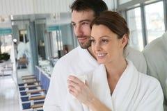 Paar in badjas het ontspannen in kuuroordcentrum stock afbeelding