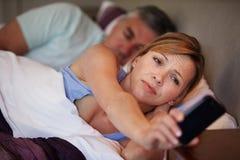 Paar in Bed met Vrouw die aan Slapeloosheid lijden Stock Fotografie