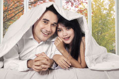 Paar behandelde deken in slaapkamer Stock Afbeelding