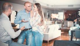 Paar berät sich mit Verkäufer, um neues Sofa zu wählen stockfotografie