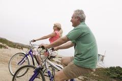 Paar berijdende fietsen op middelbare leeftijd stock afbeeldingen