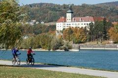 Paar berijdende fietsen op middelbare leeftijd langs de rivier van Donau Lager Oostenrijk, Europa stock foto's