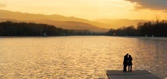 Paar bij de zonsondergang door het meer royalty-vrije stock afbeeldingen