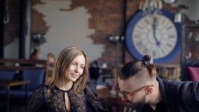 Paar bij een koffie Een mooi meisje gaat naar een vergadering met een kerel in een koffie Twee bij een lijst in een ontmoet resta stock video
